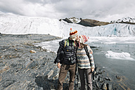 Peru, couple wearing wool chullos and kissing in front of Pastoruri glacier - GEMF000586
