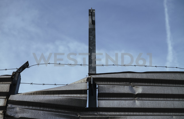 Twisted steel sheet and razor wire in front of sky - DASF000039
