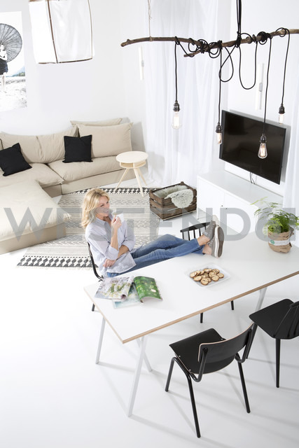 Woman sitting with feet up on the table in her livoing room drinking coffee - MAEF011213