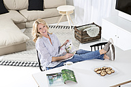 Portrait of smiling woman sitting with feet up on the table in her living room - MAEF011216