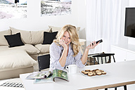 Portrait of smiling woman sitting at the table in her living room with magazines and cookies - MAEF011219