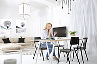 Woman sitting at the table in her living room looking at smartphone - MAEF011222