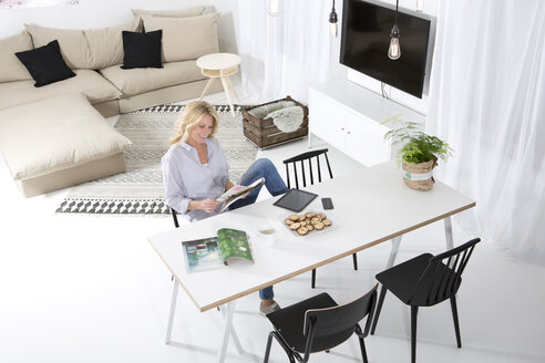 Smiling woman sitting at the table in her living room reading magazine - MAEF011225