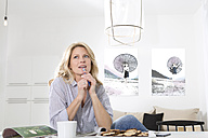 Woman sitting at the table in her living room thinking - MAEF011228