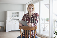 Portrait of smiling young woman with her digital tablet at home - RBF003851