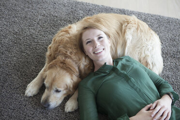 Smiling young woman relaxing with her dog on the carpet - RBF003866