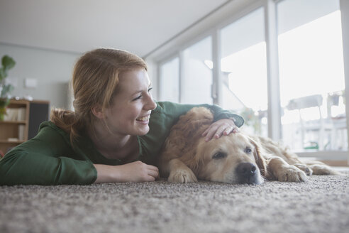 Smiling young woman lying beside her dog on the carpet - RBF003869