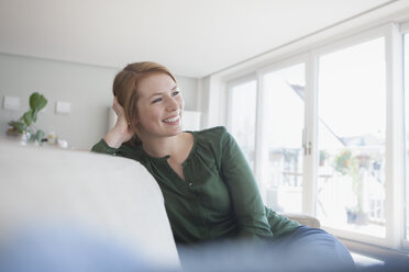 Portrait of smiling young woman sitting on the couch at home - RBF003875