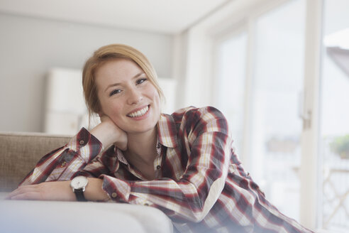 Portrait of smiling young woman relaxing at home - RBF003881