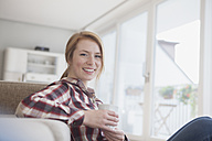 Portrait of smiling young woman relaxing with cup of coffee at home - RBF003887