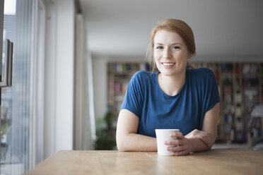 Portrait of smiling young woman sitting at table with cup of coffee - RBF003899