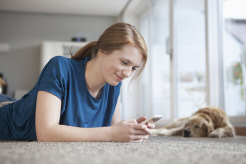 Smiling young woman lying on the floor at home looking at smartphone - RBF003905
