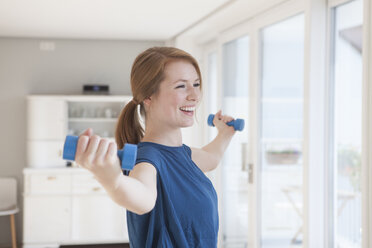 Portrait of smiling young woman exercising with dumbbells at home - RBF003908
