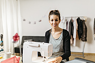 Young fashion designer working in her studio - JRFF000268