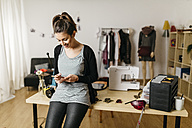 Young fashion designer working in her studio, using smartphone - JRFF000280