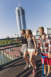 Austria, Vienna, three teenagers walking on a bridge in front of the Millenium Tower - AIF000147