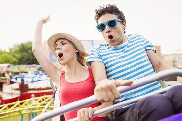 Happy couple at fun fair riding roller coaster - HAPF000098