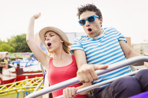 Happy couple at fun fair riding roller coaster - HAPF000098