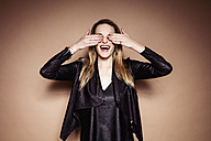 Laughing blond woman covering eyes with her hands - DAWF000400