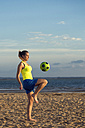 Spain, Young woman playing soccer at the beach - KIJF000083