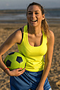 Spain, Young woman playing soccer at the beach, laughing - KIJF000089