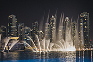 UAE, Dubai, view to skyling by night with trick fountains in the foreground - MAUF000211