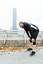 Austria, Vienna, exhausted athlete wearing earphones - AIF000155