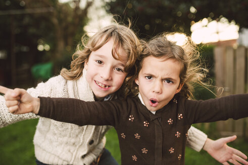Portrait of brother and little sister pulling funny faces - RAEF000764