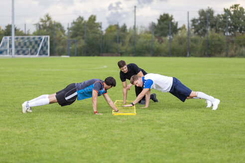 Coach exercising with soccer players on sports field - SHKF000389