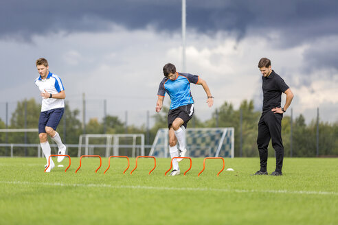 Coach exercising with soccer players on sports field - SHKF000392