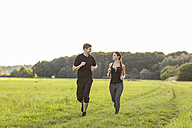 Man and woman jogging in field - SHKF000407