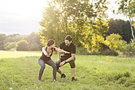 Man looking at woman doing knee bends in field - SHKF000413