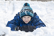 Portrait of smiling boy with bobble hat in snow - SARF002425