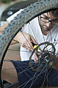 Young man installing wheel on a bicycle in workshop - SKCF000036