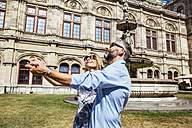 Austria, Vienna, smiling couple dancing Viennese waltz in front of state opera - AIF000166