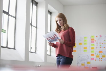 Young woman in office reading charts - RBF003915