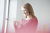 Young woman in office using smartphone - RBF003930