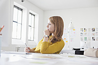 Young woman in office working at desk - RBF003942