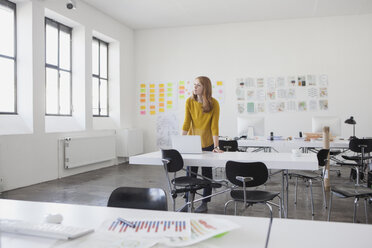 Young businesswoman standing in office, thinking - RBF003945