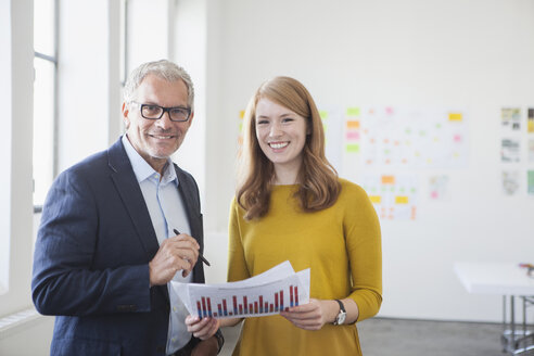 Businessman and coworker in office studying infographics - RBF003951