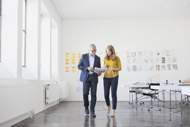 Businessman and coworker in office studying infographics - RBF003954