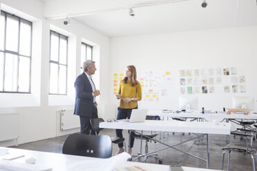 Businessman and coworker discussing project in office - RBF003957