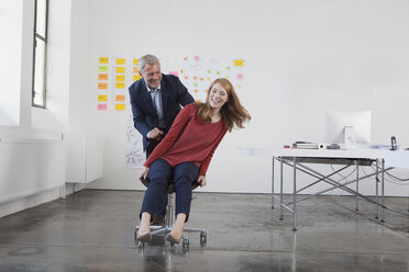 Businessman pushing young woman on chair through office - RBF003978