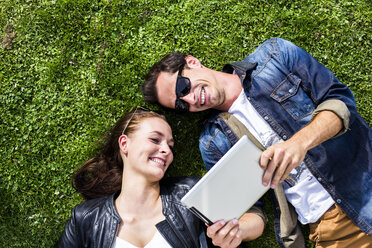 Happy young couple lying in meadow looking at digital tablet - DAWF000443