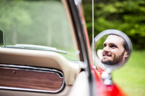 Reflection of smiling young man in wing mirror of convertible - DAWF000446
