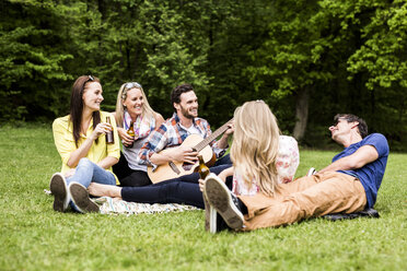 Happy friends with guitar and beer bottles relaxing in park - DAWF000452