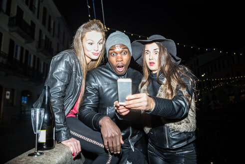 Playful friends taking a selfie outdoors at night - OIPF000064