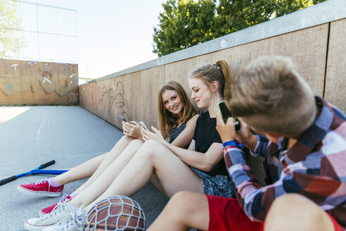 Teenage boy taking cell phone picture of friends outdoors - AIF000170