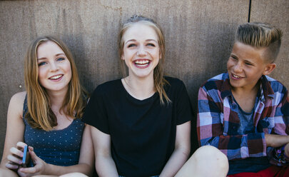 Three happy teenagers sitting outdoors - AIF000176