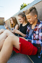 Three teenagers sitting outdoors with smartphones - AIF000179